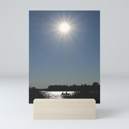 Silhouettes of two people on a rubber boat in a sunny reflection Mini Art Print