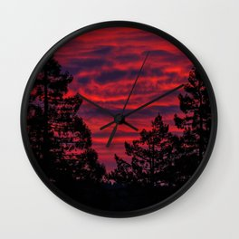 Black Trees Against a Flaming Sky Wall Clock