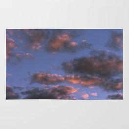 Blue sky with isolated clouds during sunset. Rug