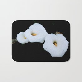 Three Calla Lilies Isolated On A Black Background Bath Mat