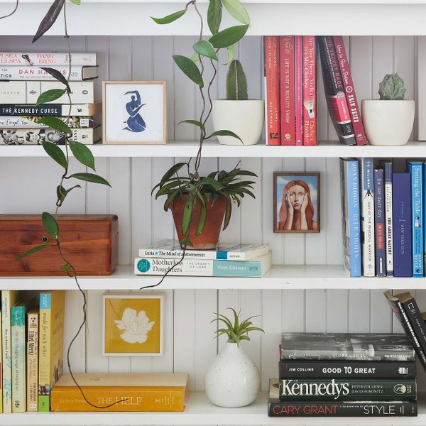 framed mini art prints and books on a white bookshelf