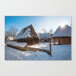 Sun warming up a traditional Romanian homestead covered in heavy snow Canvas Print