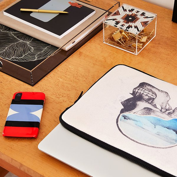 laptop sleeve and phone case on desk