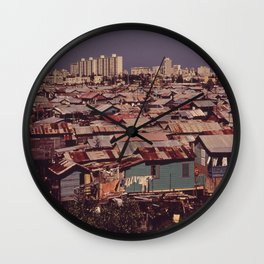 'MODERN BUILDINGS TOWER OVER THE SHANTIES CROWDED ALONG THE MARTIN PENA CANAL' Wall Clock