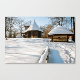 Snow cover in a Romanian Village with an old wooden church Canvas Print
