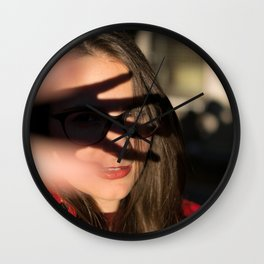 Portrait of young girl covering her face to block sun light Wall Clock