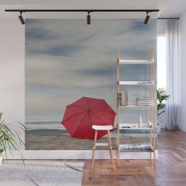Red umbrella lying at the beach Wall Mural
