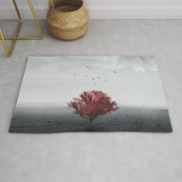 red tree in a field Rug