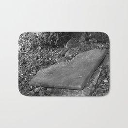 broken old grave on the green Bath Mat