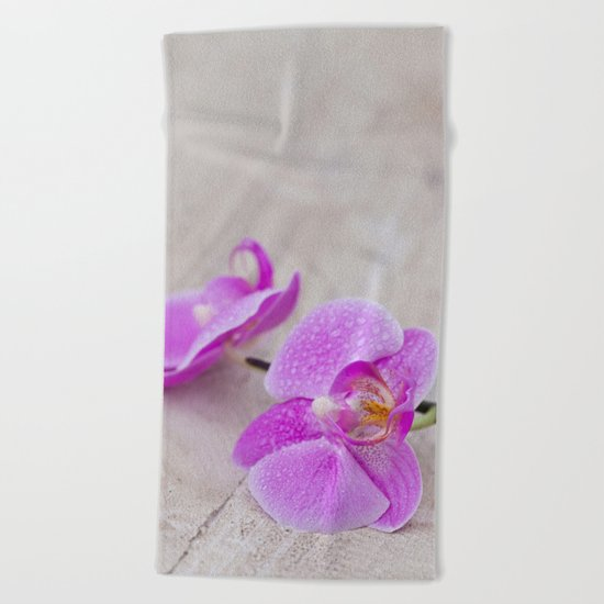 pink orchid flower close up water drops Beach Towel