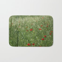 Seed Head With A Beautiful Blur of Poppies Background Bath Mat