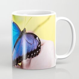 Morpho butterfly sitting on the human hand Coffee Mug