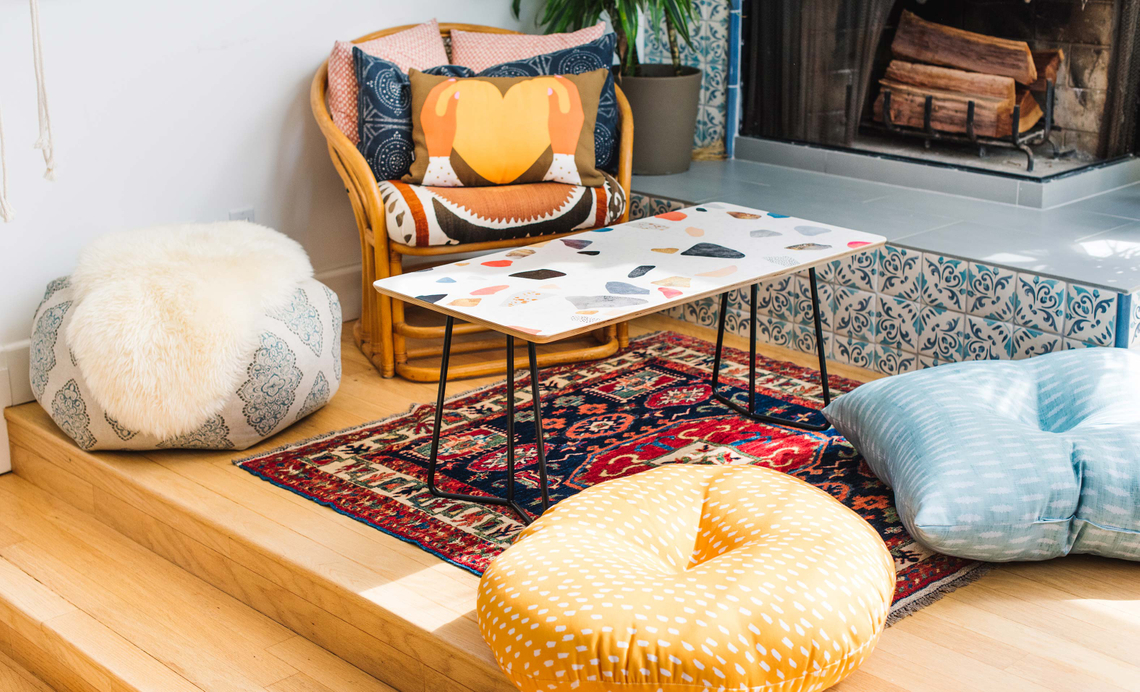 living room with boho floor pillows and terrazzo patterned coffee table