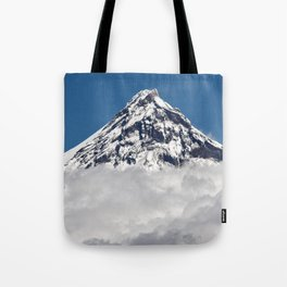 Stunning snowy top of rocky volcanoes cones above clouds. Beautiful mountain landscape of Kamchatka Tote Bag