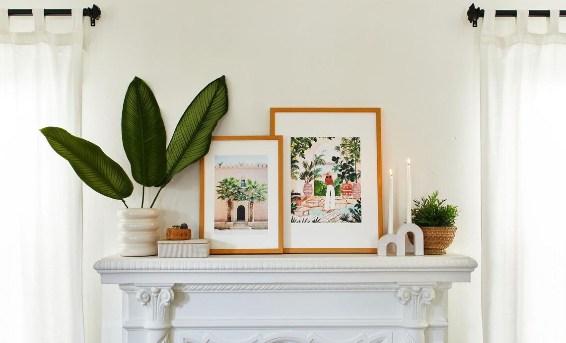 boho framed prints on a mantel next to plants