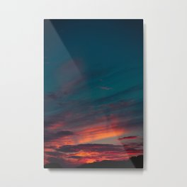 Beautiful gray clouds illuminated in red by the sunset sun. Ahead some dark bushes. Metal Print