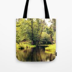 a tree by the river Tote Bag