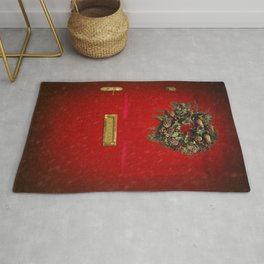 Christmas decorative wreath hung on red Victorian door with winter snow. Rug