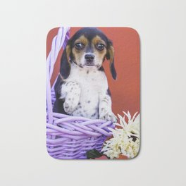 Tricolor Beagle Puppy Holding up Her Paw in a Purple Basket with Flowers in Front of Red Background Bath Mat