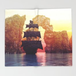 A pirate ship off an island at a sunset Throw Blanket