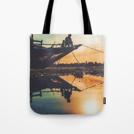 Kid sitting on a boat during the sunset Tote Bag