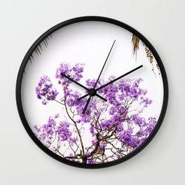 Purple jacaranda tree with palm tree leaves with a white sky Wall Clock
