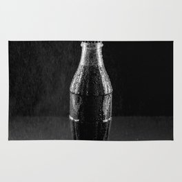 Glass bottle with carbonated drink under the drops of water. Rug