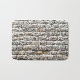 Close up view of the textured stone wall of a historical building Bath Mat