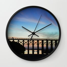 Couple watching the sunset while childeren play in the water underneath them Wall Clock
