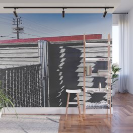 steel fence and wooden fence with red building in the city Wall Mural