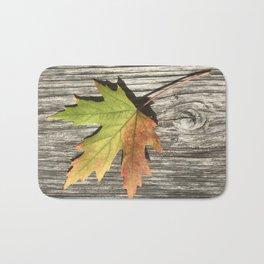 Fall leaf on weathered wood Bath Mat