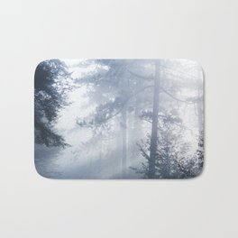 Sun rays shinning through foggy forest Bath Mat