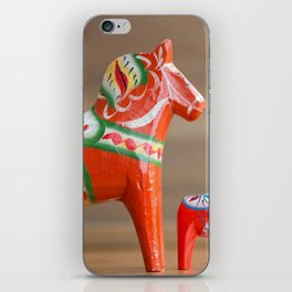 Three Dalahorses in decreasing sizes in a row close side view iPhone Skin