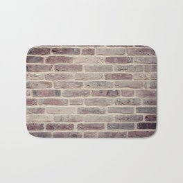 Wall built with bricks of various earth tones Bath Mat