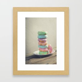 A stack of donuts on wooden table against the wall Framed Art Print