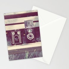two cameras sitting on a park bench ...  Stationery Cards