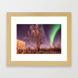 Green northern lights with tree in the middle over the Kiruna town in Sweden. Framed Art Print