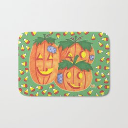 Halloween pumpkins and candy corn on green Bath Mat