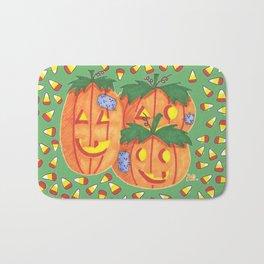 Halloween pumpkins and candy corn on green Bath Mat