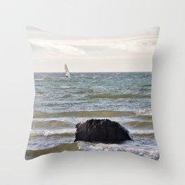 Windsurfer and black stone at gray sea Throw Pillow