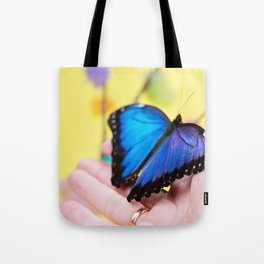 Morpho butterfly sitting on the human hand Tote Bag