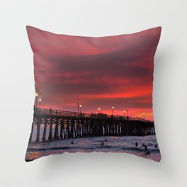Surfers riding waves off Seal Beach pier at sunset Throw Pillow