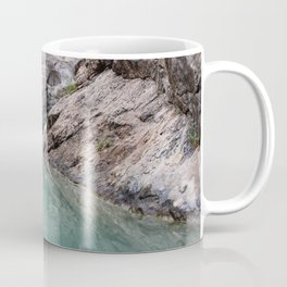 The rocks are reflected in the emerald water of a mountain lake. Coffee Mug