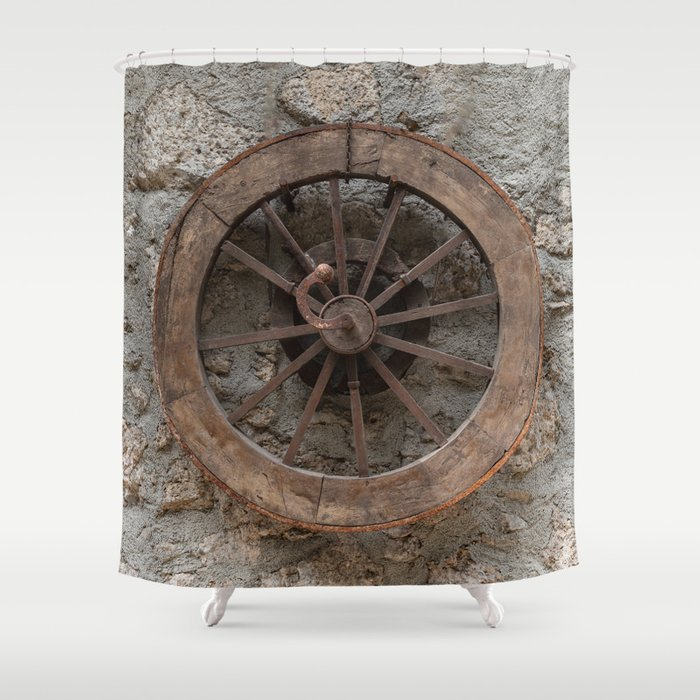 Wooden wheel hanging on a stone wall Shower Curtain
