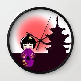 Japanese kokeshi doll at temple during sunset Wall Clock