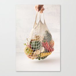 Woman's hand holding a cotton bag of mixed fruit and vegetables Canvas Print