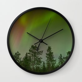 Ethereal multicoloured lights over a forest Wall Clock