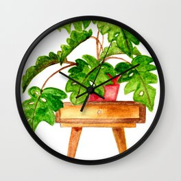 Monstera on a table Wall Clock