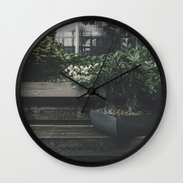 Potted plant on a wooden plank in the garden Wall Clock