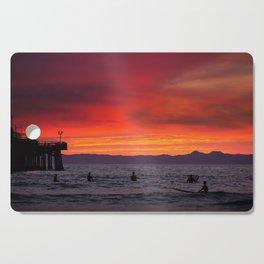 Surfers watching Sunset Cutting Board